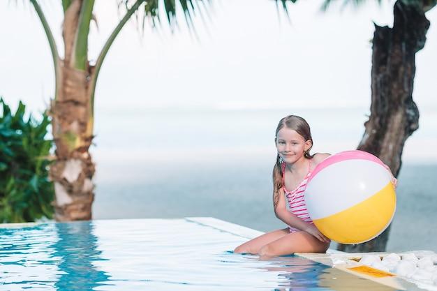 屋外スイミングプールで膨脹可能なおもちゃのボールで遊ぶ愛らしい少女の笑顔
