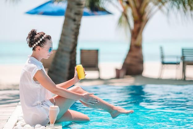 Молодая женщина, применяя солнцезащитный крем во время пляжного отдыха