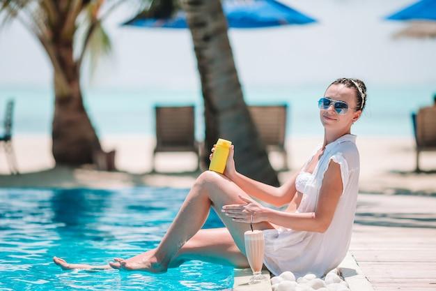 ビーチでの休暇中に日焼け止めを適用する若い女性