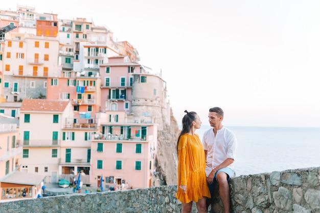 Счастливая пара фоне потрясающей деревни манарола, чинкве-терре, лигурия, италия