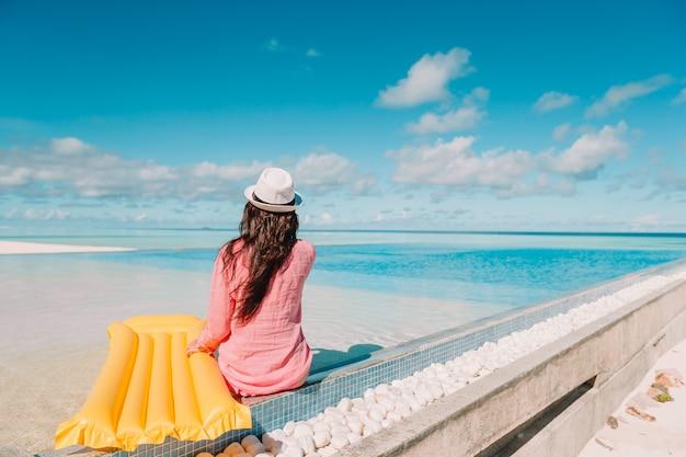 スイミングプール、高級ホテルの屋外プールで幸せな女の子でリラックスした美しい若い女性