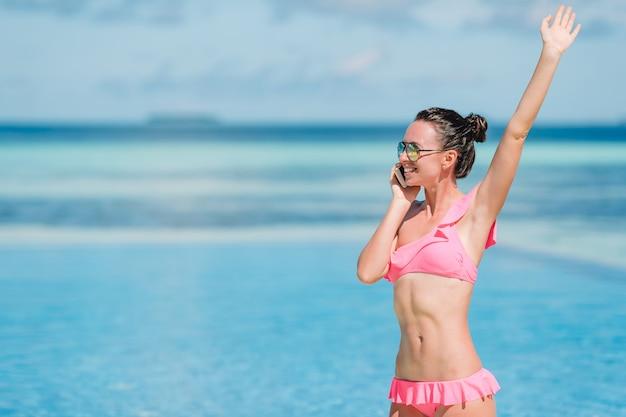 白いビーチに電話で話している若い美しい女性