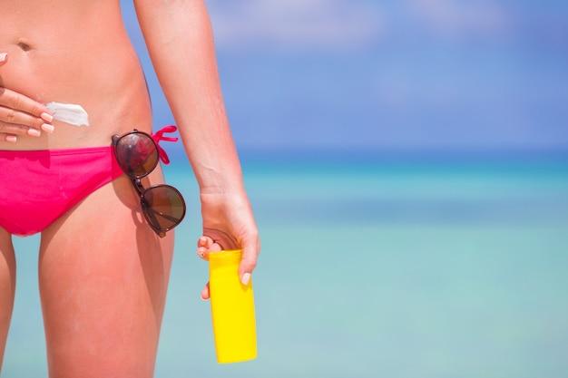 白いビーチに日焼け止めで胃を適用する若い女性