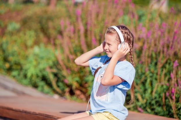 愛らしい少女が公園で音楽を聴く