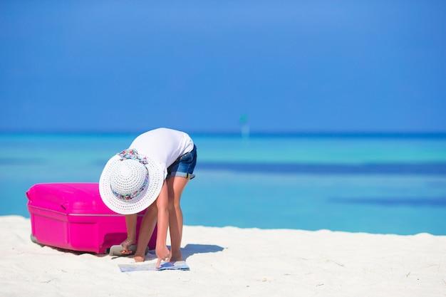 Маленькая прелестная девушка с большим багажом и карта острова на белом пляже