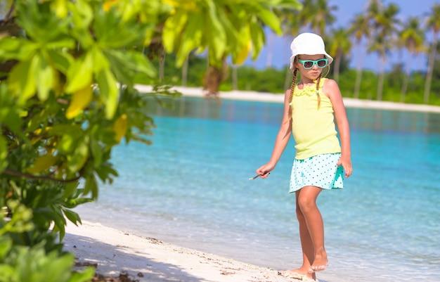 白いビーチに絵を描く愛らしい幼児の女の子