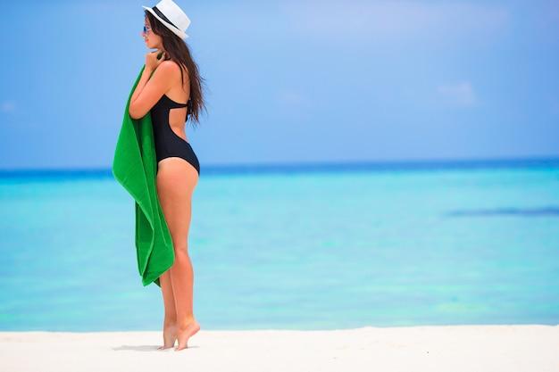 白い砂浜でタオルに包まれた若い女性