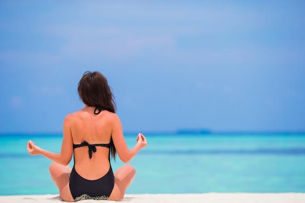 ビーチで瞑想ヨガの位置に座っている健康な若い女性