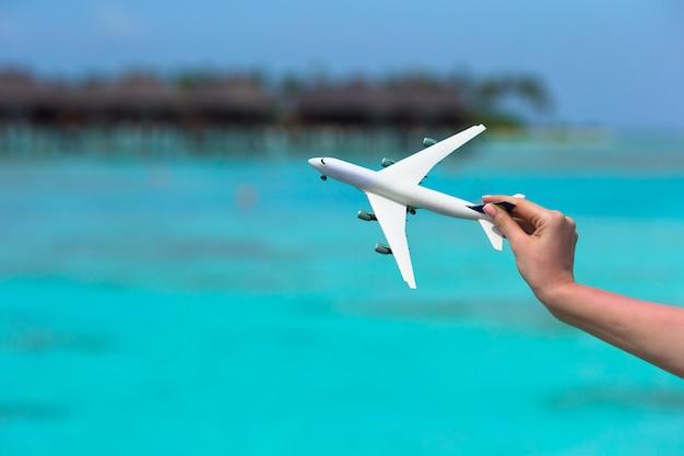 ターコイズブルーの海の小さな白いおもちゃの飛行機