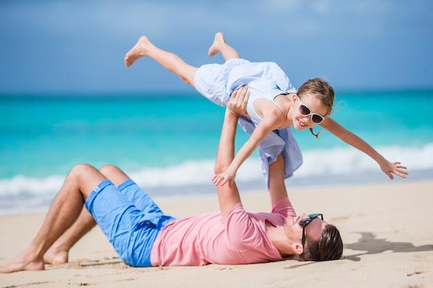 父とビーチで楽しんでスポーティな少女の家族