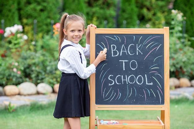 屋外の黒板との幸せな小さな女子高生