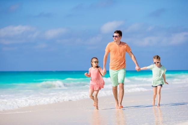 カリブ海の島の白い熱帯のビーチを歩いて家族