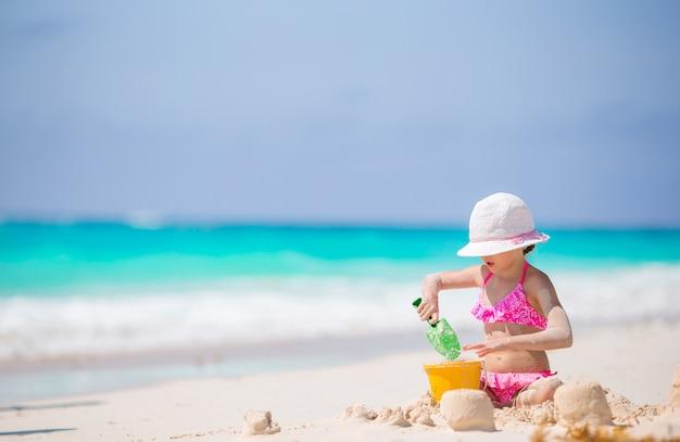 Прелестная маленькая девочка играя с игрушками пляжа на белом пляже