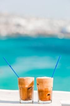 海の背景を持つ木製のテーブルの上のコーヒーカフェラテ