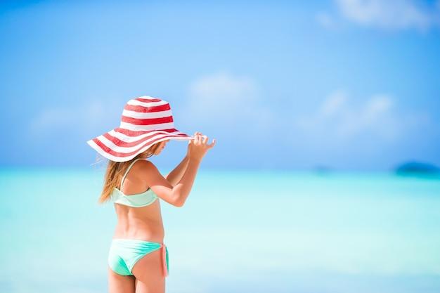 Очаровательная маленькая девочка в большой красной шляпе на пляже