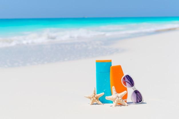サンクリームボトル、サングラス、白い砂の背景の海のヒトデ