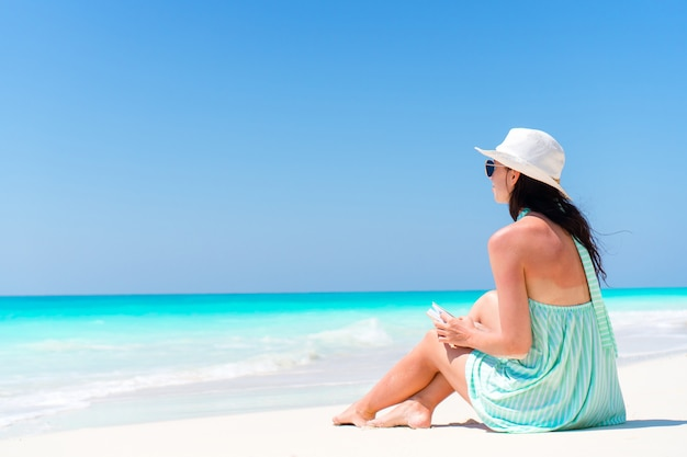 Женщина сидит на пляже, наслаждаясь летними каникулами