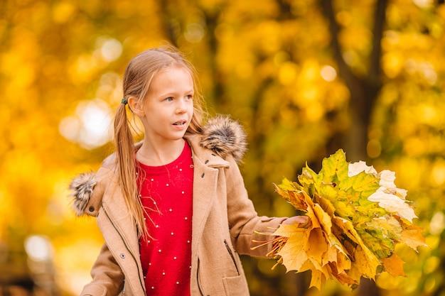Портрет очаровательны маленькая девочка с желтыми листьями букет осенью