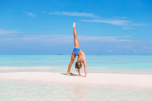 Очаровательная маленькая девочка с удовольствием делает колесо на тропическом белом песчаном пляже
