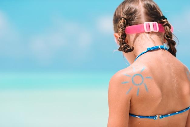 子供の肩に太陽のクリームで塗られた太陽を閉じる