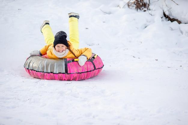 冬の雪の日にそりの愛らしい小さな幸せな女の子。