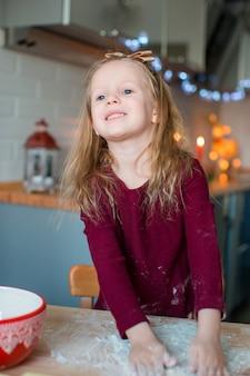 Очаровательная маленькая девочка, пекущая рождественские пряники
