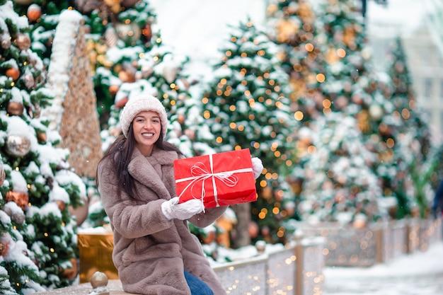 Счастливая девушка возле еловые ветви в снегу на новый год.