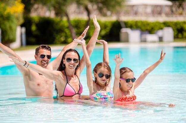 Счастливая семья из четырех человек в бассейне