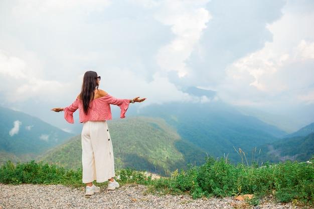 霧のシーンの山の美しい幸せな若い女性
