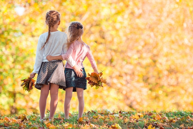 Маленькие очаровательные девушки на улице в теплый солнечный осенний день