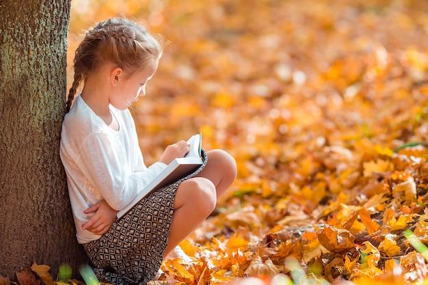 Портрет очаровательны маленькая девочка на улице в красивой осени