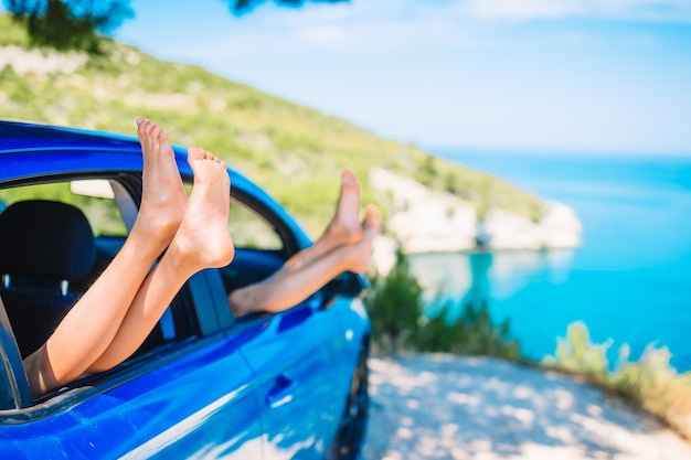 夏休み、休日、旅行、道路旅行、人々の概念-車の窓から示す小さな女の子の足のクローズアップ