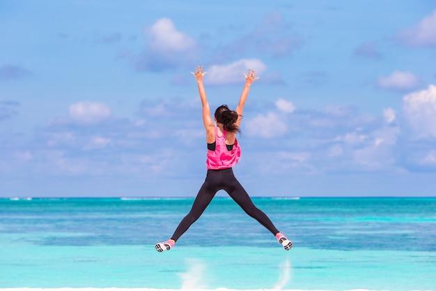 Подходит молодая женщина делает упражнения на тропическом белом пляже в своей спортивной одежде