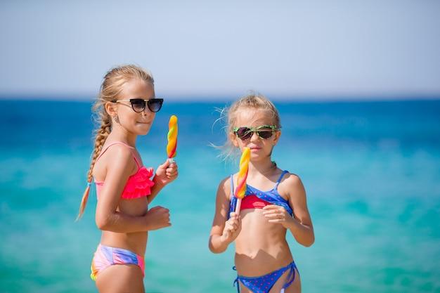 Счастливые маленькие девочки едят мороженое во время пляжного отдыха