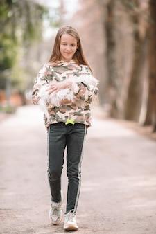 Маленькая девочка с белым щенком. щенок в руках девочки