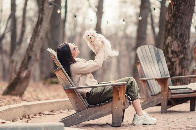 Женщина с белым щенком. щенок в руках красивой девушки