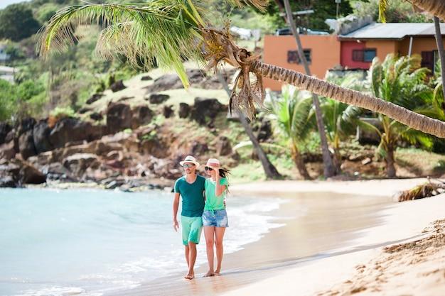 熱帯のカーライルベイビーチの上を歩く若いカップル