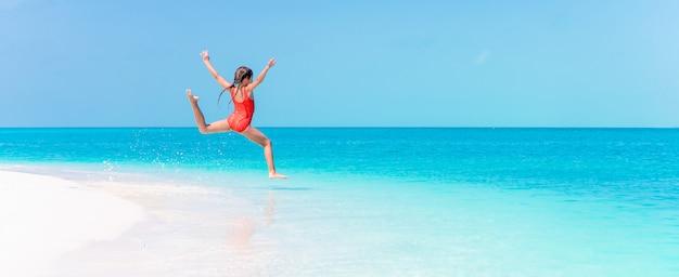 Портрет очаровательны маленькая девочка на пляже во время летних каникул