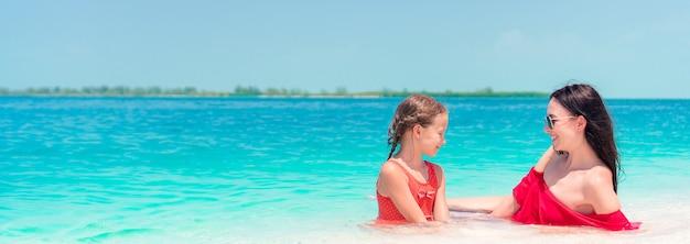 母と熱帯のビーチでの時間を楽しんでいる小さな娘