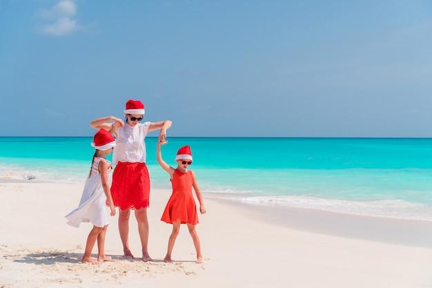 Счастливая мама и маленькие девочки в новогодней шапке на летних каникулах