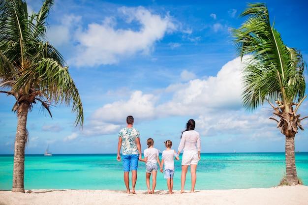 Семья из четырех человек на пляже на карибских каникулах.