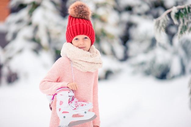 Милый маленький ребенок девочка собирается кататься на коньках на открытом воздухе.