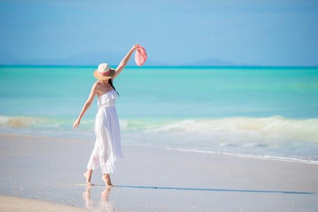 Молодая красивая женщина на тропическом пляже с белым песком.
