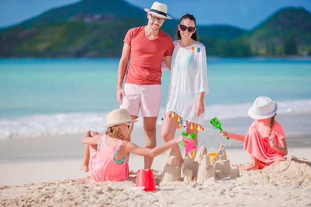 Семья делает замок из песка на белом пляже на летние каникулы
