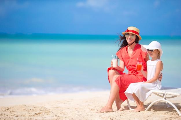 Семья на пляже, сидя на шезлонгах
