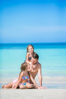 Отец и дети наслаждаются летними каникулами на пляже