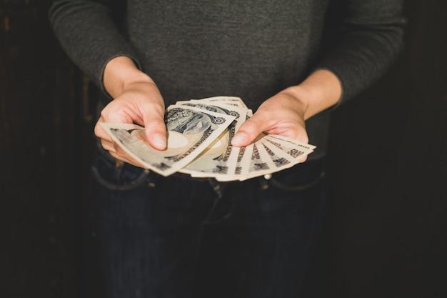 日本円のお金を数える手。ショッピング、支払いの概念、収入およびビジネスの概念。