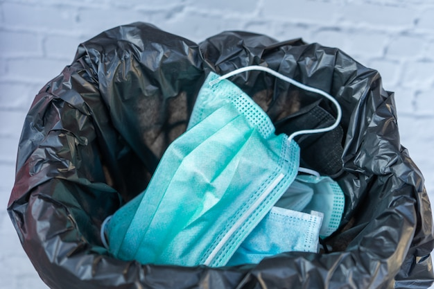 Утилизация использованной маски в мусорном баке. оставляя негигиеничными, возможно распространение вредных микробов и вирусов. концепции здравоохранения