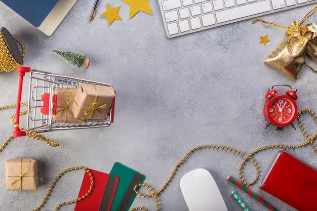 赤い時計、青いノートブック、キーボード、バスケット、クレジットカードでプレゼントを上から見る。
