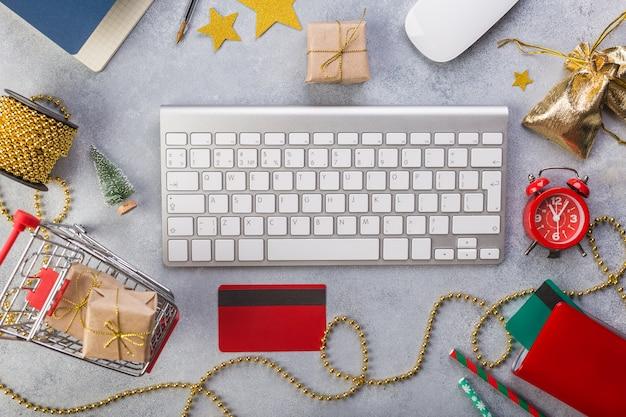 Взгляд сверху с красными часами, голубой тетрадью, клавиатурой, подарками в корзине, кредитными карточками.